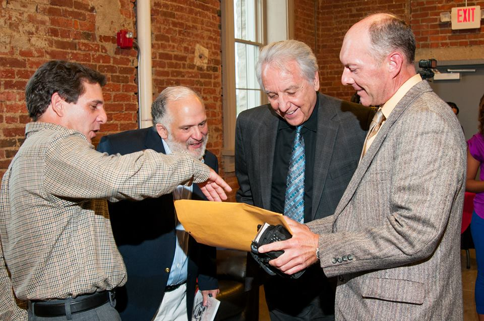 Author Brad Mavis and Jodiviah Stepp showing actors Frank Medrano (Fat Ass) and Bob Gunton (Warden Norton) a copy of <i>Rita the Shawshank Dog.</i>