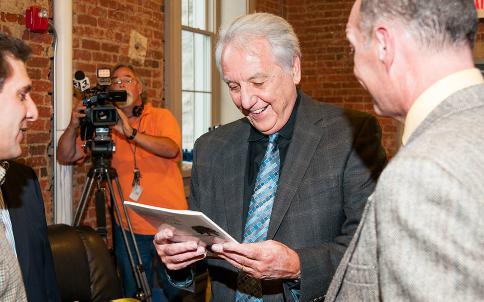 Author Brad Mavis and actor Jodiviah Stepp present actor Bob Gunton (Warden Norton) a copy of <i>Rita the Shawshank Dog.</i>